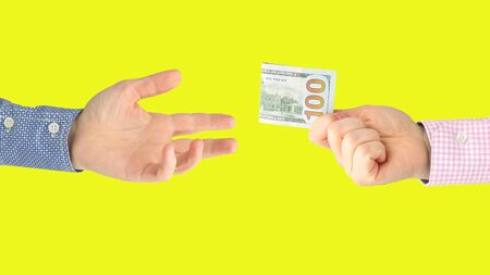 man's hand holds out a fork with a dollar bill in the other hand on yellow background Reklamní fotografie