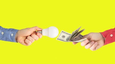 two hands with dollar bills and led lamp on a bright orange background. Payment for electricity. Buy led lamp. Business industry