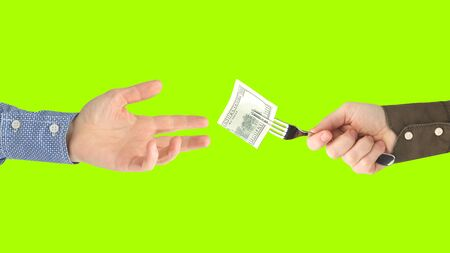 man's hand holds out a fork with a dollar bill in the other hand on lime background