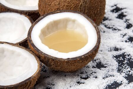 cut fresh coconut with real coconut milk on a dark background of coconut flakes. vitamin fruits. healthy food