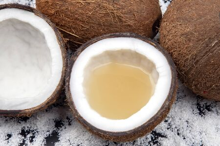 cut fresh coconut with real coconut milk on a background of coconut flakes. vitamin fruits. healthy food Archivio Fotografico