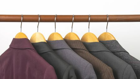 Different womens office classic jackets hang on a hanger for storing clothes. The choice of style of fashionable clothes.