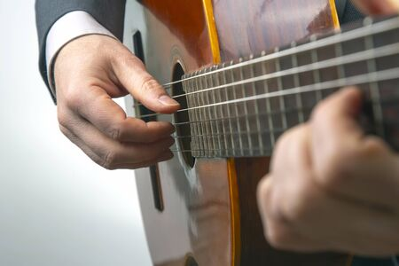 man plays the classical guitar on a white background. musical creativity. string musical instrument