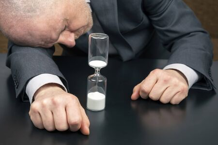 hourglass on the background of a tired and depressed business man. distribution of time for work. time to make decisions. late business opportunities