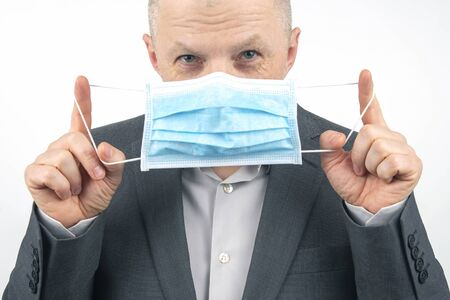 man in a business suit suggests using a medical protective mask in quarantine during an epidemic of coronavirus. Stock fotó