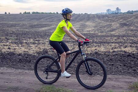Schöner Mädchenradfahrer fährt Fahrrad auf dem Feld. Gesunder Lebensstil und Sport. Freizeit und Hobbys