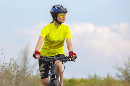 Beautiful girl in yellow riding a bike in nature. Sports and recreation. Hobbies and health. Stock Photo