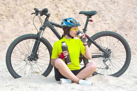 Beautiful girl cyclist pours tea  on the background of a Bicycle in the sand. Sports and recreation. Hobbies and health. Nature and man