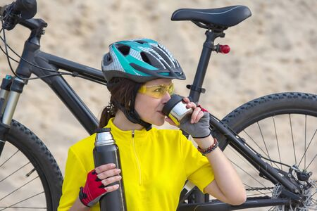 Beautiful girl cyclist in yellow with tea   in hand on the background of sand. Sports and recreation. Nature and man Stock Photo
