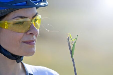 Beautiful girl cyclist holding a mantis beetle. Nature and man Stock Photo
