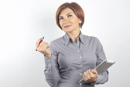 Beautiful young business girl with a red pen and a tablet in hands on a white background