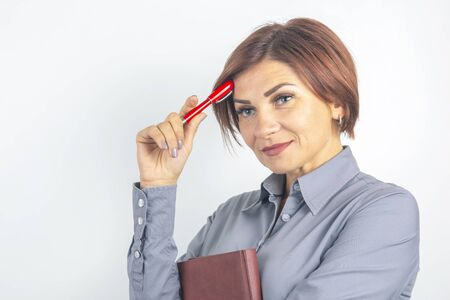 Beautiful young business girl with a red pen in hand on a white background