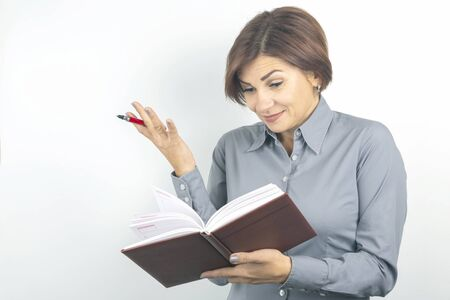 Beautiful young business girl with a red pen and notebook in hands on a white background Stock Photo