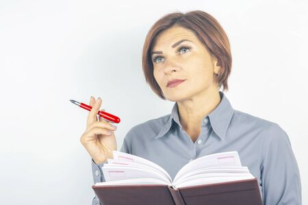 business girl with a red pen and notebook in hands on a white background