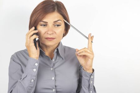 Business beautiful woman speaks on the phone with a pencil in her hand on a white background Stock Photo