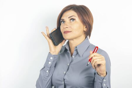 Business beautiful woman speaks on the phone with a pen in her hand on a white background