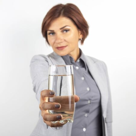 Happy beautiful business woman offers a glass of water. Thirst and health.