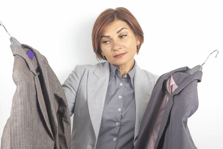 Beautiful business woman chooses office clothes from different jackets. Fashion and beauty in clothes.