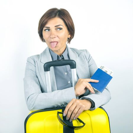 Happy beautiful business woman with passport and baggage going on a trip. Vacation and entertainment. Search for places to travel. Show tongue.