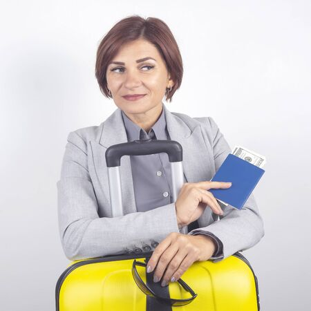 Happy beautiful business woman with passport and baggage going on a trip. Vacation and entertainment. Search for places to travel.