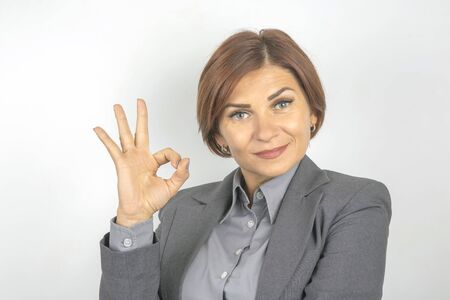 Business woman in suit shows ok sign with hands