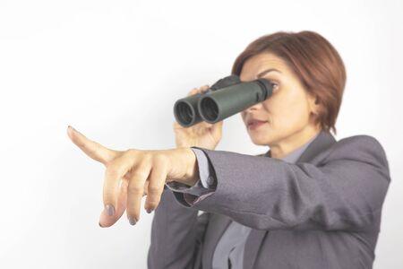 Business woman in suit looking through binoculars
