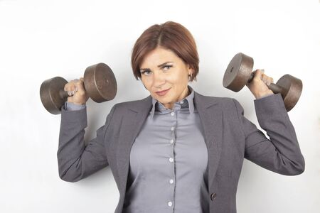 Happy beautiful business woman in a suit lifts dumbbells on a white background. Fitness and health. career growth and work Stock Photo