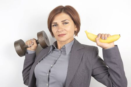 Happy beautiful business woman in a suit lifts a dumbbell and a banana in her hands. Fitness and health. Proper nutrition and excellent results.
