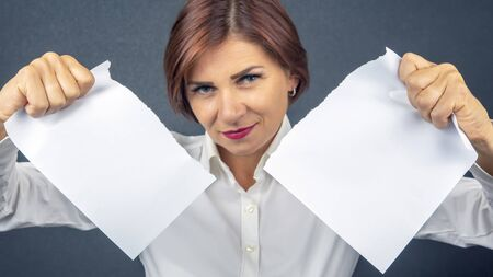 Beautiful business woman tearing white paper in half