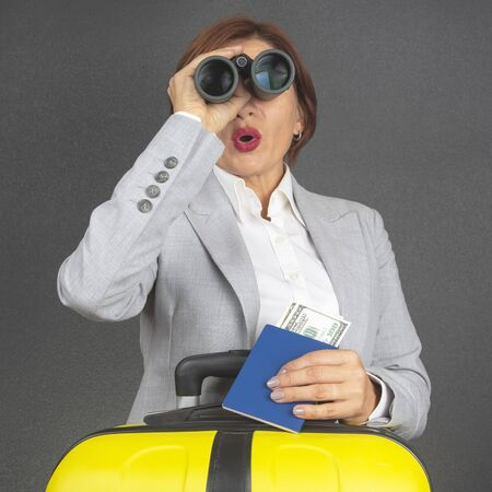 Happy beautiful business woman looks with binoculars in surprise towards her travel. Vacation and entertainment. Search for places to travel. Stock Photo