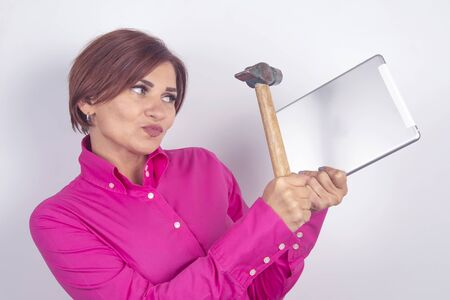 Business woman in a shirt smashes a tablet in her hands with a hammer. Stock Photo