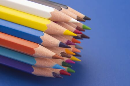 set of color pencils on a blue background. drawing tools. a palette in creativity