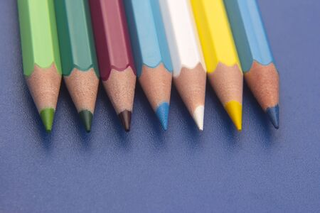 set of color pencils on a blue background. drawing tools. palette in creativity