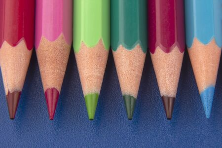 Colored pencils for drawing on a dark blue background. Education and creativity. Leisure and art