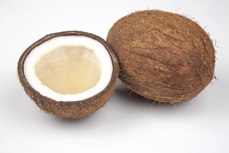cut fresh coconut with real coconut milk on a white background. vitamin fruits. healthy food
