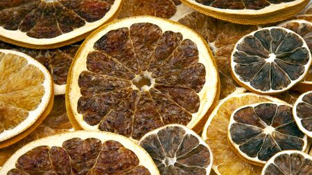 Dried slices of various citrus fruits on dark blue background
