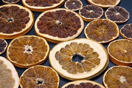 Dried slices of various citrus fruits closeup on dark blue background