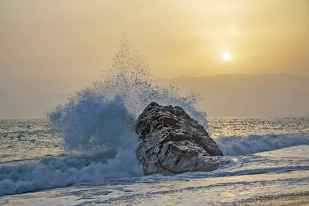 Sea wave beating with force against the rock at sunset Archivio Fotografico