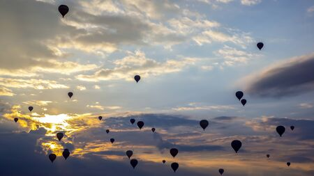 Many passenger balloons fly against the background of dawn in the clouds