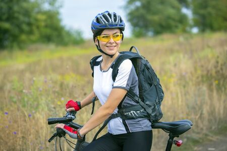 Beautiful girl cyclist with a bicycle on the nature. Healthy lifestyle and sport. Leisure and hobbies
