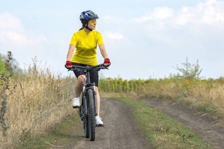 Beautiful girl in yellow riding a bike in nature. Sports and recreation. Hobbies and health. Archivio Fotografico