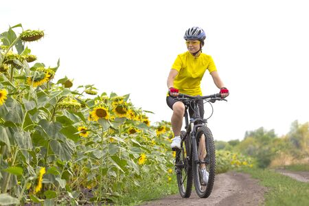 Beautiful girl cyclist rides a field with sunflowers on a bicycle. Healthy lifestyle and sport. Leisure and hobbies