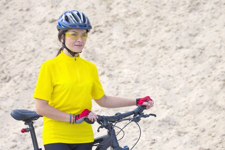 beautiful girl cyclist with bike against the background of the Sands. sports and recreation. Nature and man