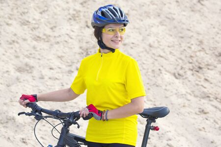 beautiful girl cyclist with bike against the background of the Sands. sports and recreation.