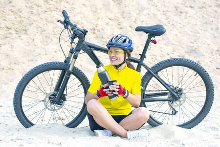 Beautiful girl cyclist pours tea from a thermo on the background of a Bicycle in the sand. Sports and recreation. Hobbies and health.