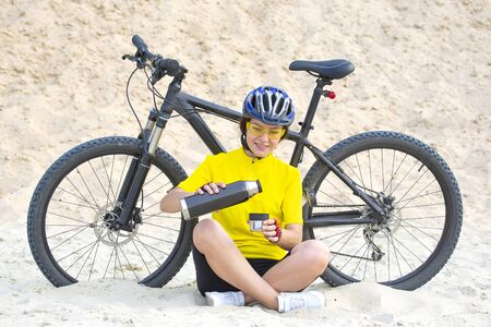 Beautiful girl cyclist in yellow with tea and thermo in hand on the background of sand. Sports and recreation.