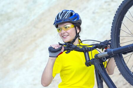 beautiful girl cyclist with bike against the background of the Sands. sports and recreation Archivio Fotografico