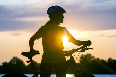 Silhouette of a girl cyclist with a bicycle on the background of a sunset sky. Healthy lifestyle and sport. Leisure and hobbies