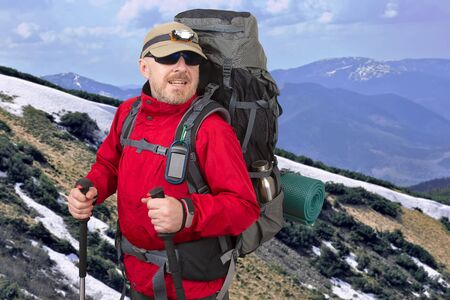 Happy tourist with backpack is traveling in the highlands. mountain range covered with snow