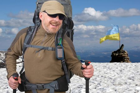 Happy tourist with backpack is traveling in the highlands. beautiful snow mountain wide range